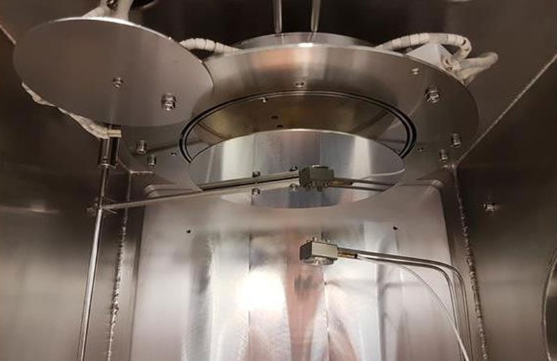 Close-up of MiniLab 090 chamber ceiling with substrate shutter, water-cooled quartz crystal sensor head and heating stage for 500 °C platen temperatures